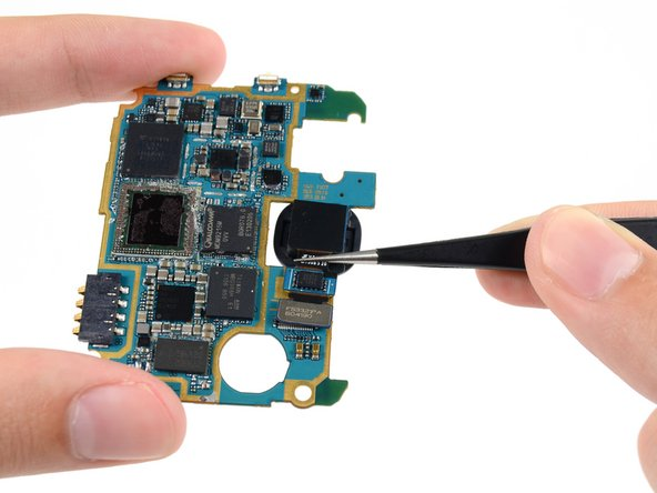Using tweezers, or your fingers, slide the rear-facing camera out of its notch in the motherboard.