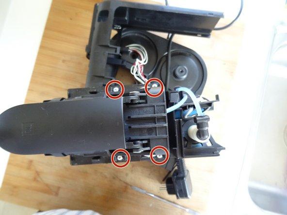Die Brüheinheit ist mit vier Torx T10 Schrauben befestigt. Drehe sie heraus.