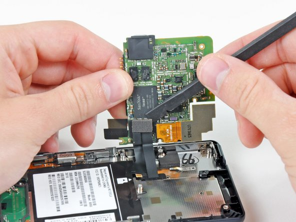 Carefully lift the motherboard from the front case and lay it next to the Droid 2, minding the keypad connector that is still attached.