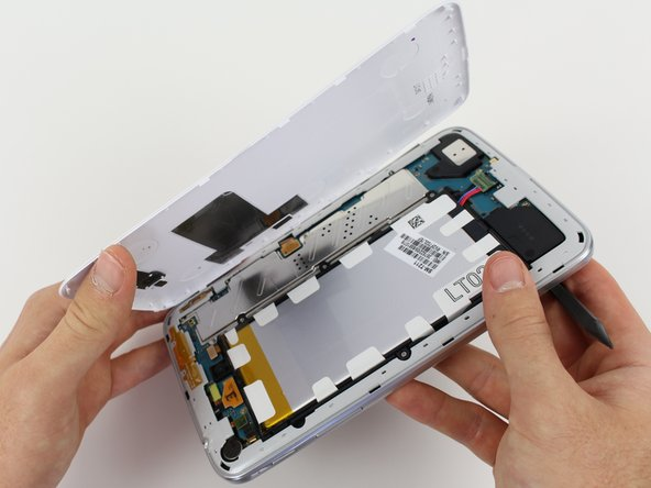 Once the backing has been pried off all around the device, remove the white backing.