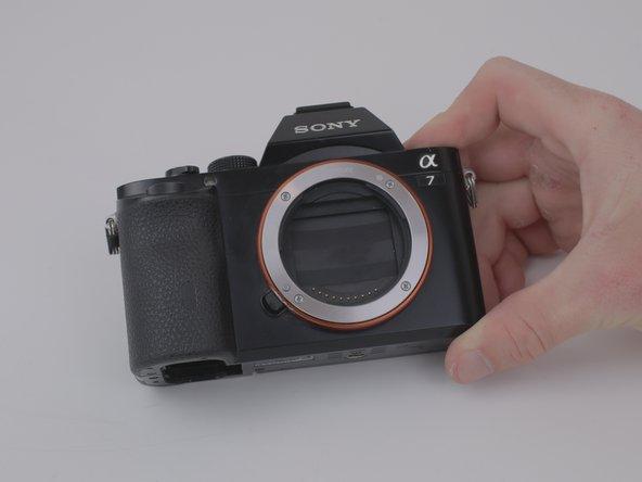 Positionnez la caméra de façon à ce que l'objectif et le logo «SONY» avant soient tournés vers l'avant et à la verticale.
