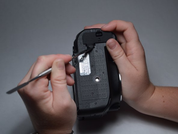 Using a spudger or other prying tool, gently pop the battery door off of its hinge.