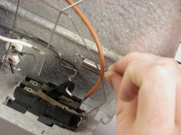 Remove the spring from the door mechanism by pulling it off.