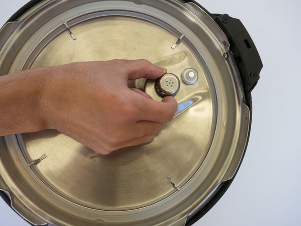 Pinch the anti-block shield and twist counterclockwise while pulling up and out from the lid.