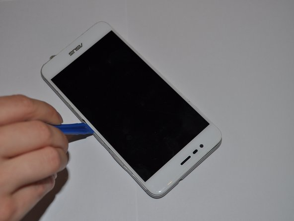 Using an iFixit opening tool, gently wedge the tool between the phone and the back casing.
