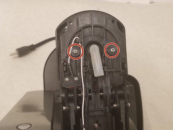 Using a Phillips #2 screwdriver, remove the two 9.0 mm screws next to the detached tube.