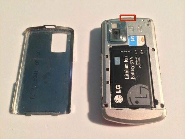 Push on the button on the top of the phone to release the battery cover.