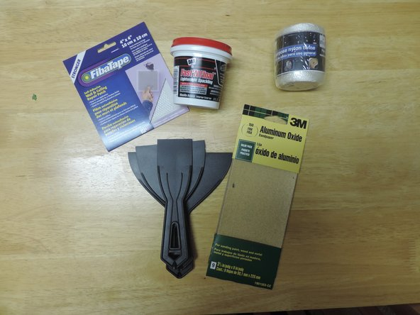 For this fix, you will need (from left to right): an adhesive wall repair patch, spackle, string, a putty knife, and sand paper.