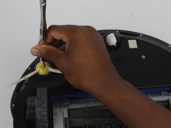 Using the Phillips #2 screwdriver, remove the screw connecting the side brush to the device.
