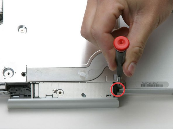 Pull the optical drive out just enough so that you can access and remove a Phillips screw near the battery compartment.
