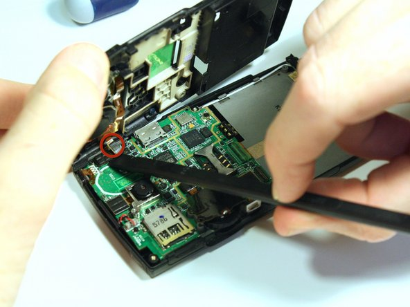 Use the spudger to unsnap the gold wire connection that connects the back casing to the logic board.
