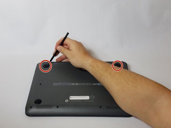 Use the nylon spudger to remove the rubber pads near the hinge for the screen. Then remove the screws under the pads.