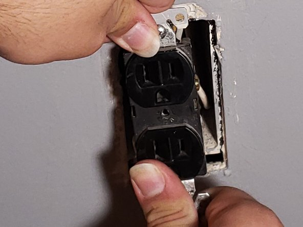 Holding the top and bottom tabs of the outlet, pull the outlet away from the wall, exposing the wires inside the electrical box.