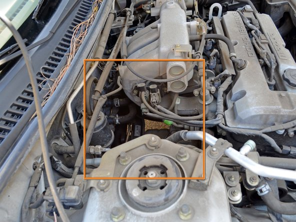 On the back passenger side of the engine bay, you will find a space where you can see the back of the engine.
