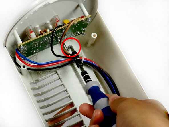 Remove the Phillips 6-mm screw that holds the circuit board to the outer shell of the fan.
