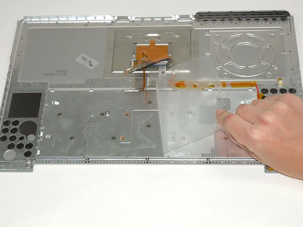 Peel back the clear plastic shielding covering the keyboard screws.