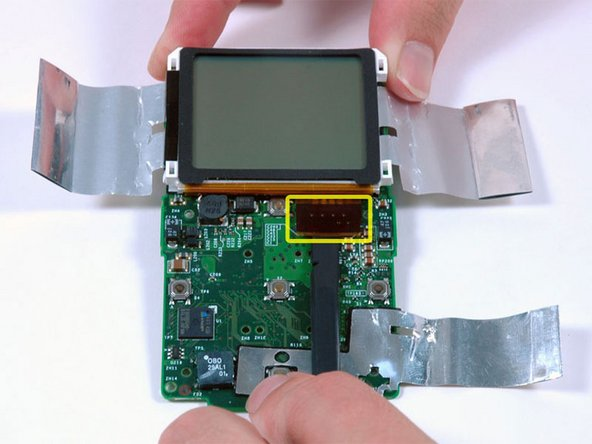 Use a spudger to carefully disconnect the display ribbon cable from beneath the scroll wheel.