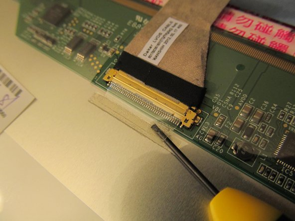 Gently pry the small piece of tape away from the back of the LCD. This tape helps keep the LCD cable intact.