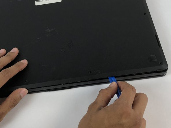 Carefully insert a plastic opening tool under one corner of the back panel.