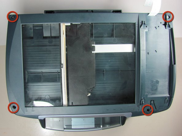 Remove all four silver screws from the corners of the scanner glass cover with a T10 Torx Screwdriver.