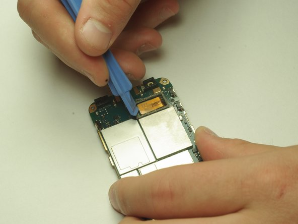 Use the plastic opening tool to pry the ribbon cable away from the motherboard.