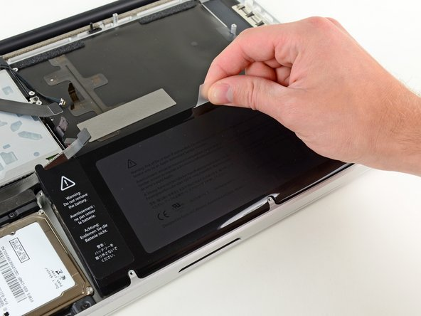 Use the attached plastic pull tab to remove the battery from the upper case.