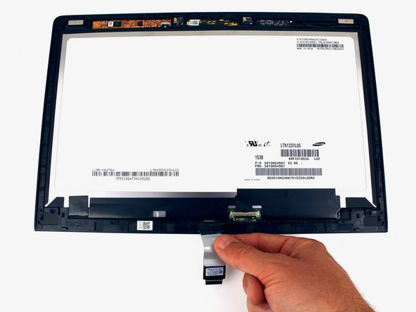 Gently pull the cable out from the routing to free it from the hooks along the edge of the screen.