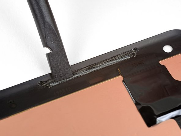 Use the flat end of a spudger to push the top of the grille down against the adhesive strip.