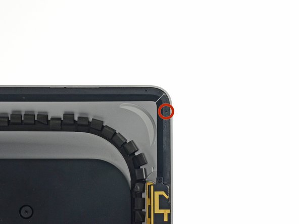 With the spudger still poking through the hole in the adhesive strip, push the spudger tip into the corresponding hole in the frame of the iMac.