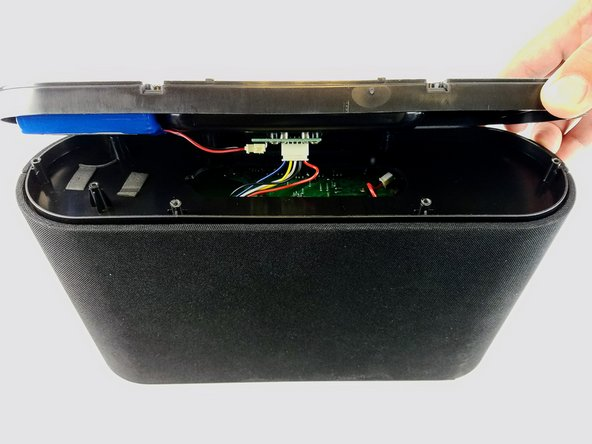 Lift the base up gently keeping in mind that the base is connected with wires to internal parts of the speaker.