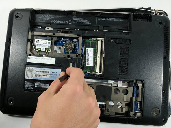Push on the rear end of the CD drive with a small non-metallic item to free it from the case