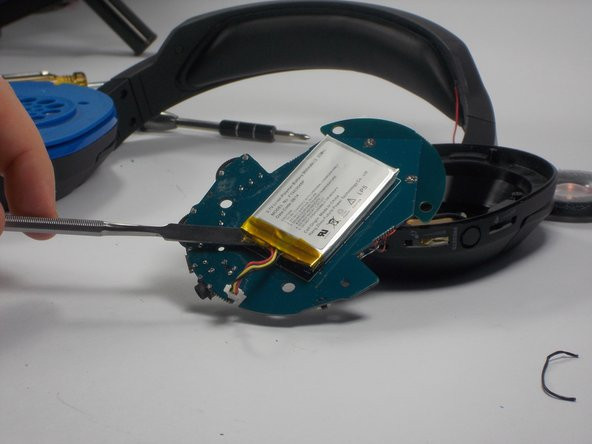 Use metal pry tool to slide between battery and circuit board to break up adhesive. Ensure the battery wire connector plug has been removed on front side.