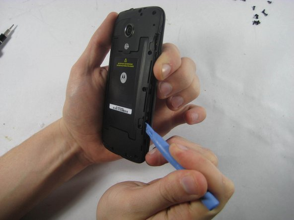 Use a plastic opening tool to remove the  protective cover.