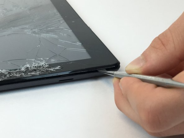 Pry the plastic backing off of the tablet using the plastic spudger, releasing all interior clips.