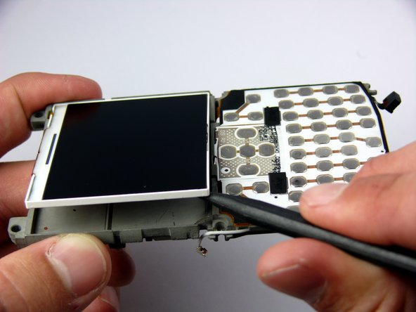 There is a hanging ribbon cable connected to the LCD screen that passes through the LCD frame.