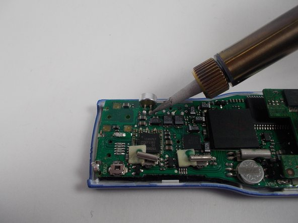 Use the soldering iron to liquefy the solder connecting the microphone to the motherboard.