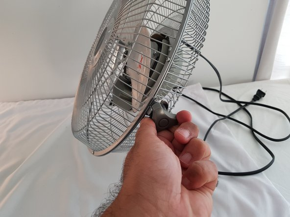 Remove the clamp on one side of the fan by turning it counterclockwise.