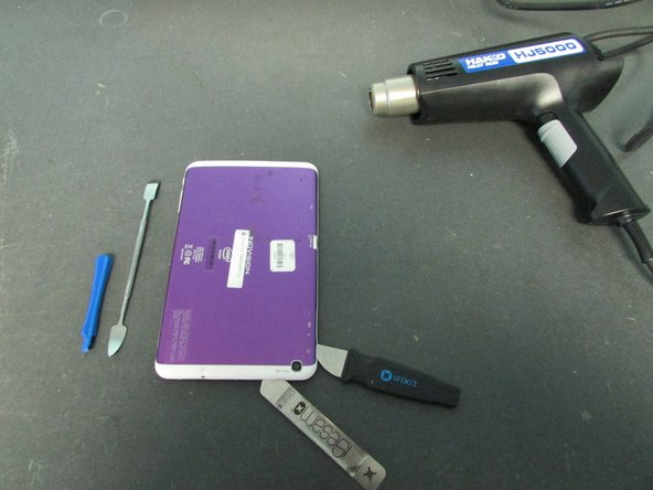 Use a Heat Gun to loosen the adhesive on the underside of the back cover.