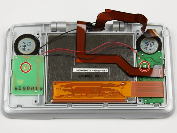 Using a Phillips #00 screwdriver, remove the two screws holding down the speaker circuit boards.