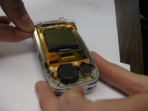 Slide out the two metal braces located along the sides of the LCD screen.