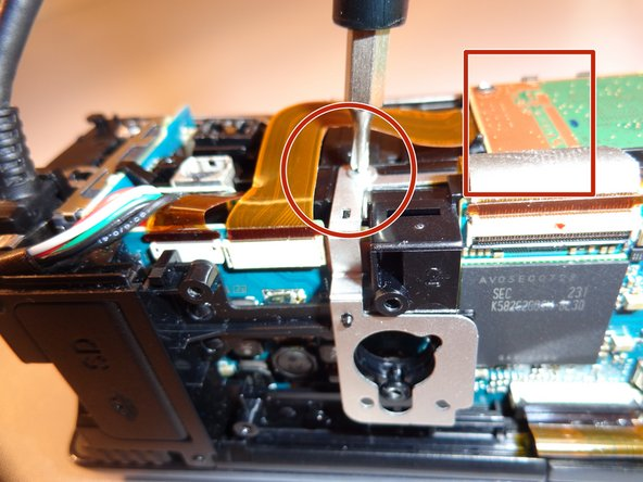 Remove three black 5 mm screws and one silver 4 mm screw on the front right of the camera, where the orange motherboard is.