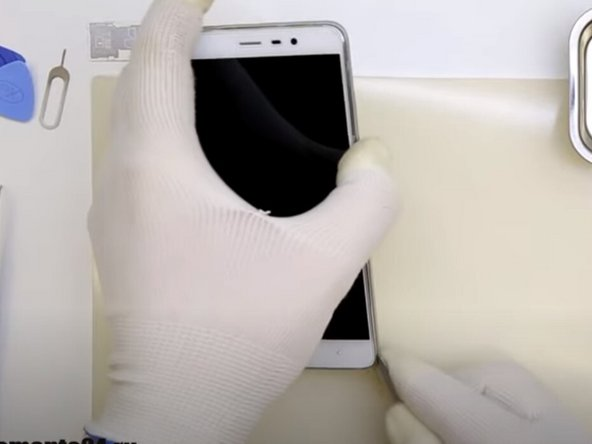 Insert a putty knife or opening tool into the seam between the phone's back cover and front cover.