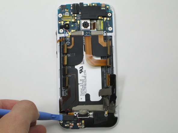 Using the narrow plastic prying tool, pry up the rectangle connector covered in black foam