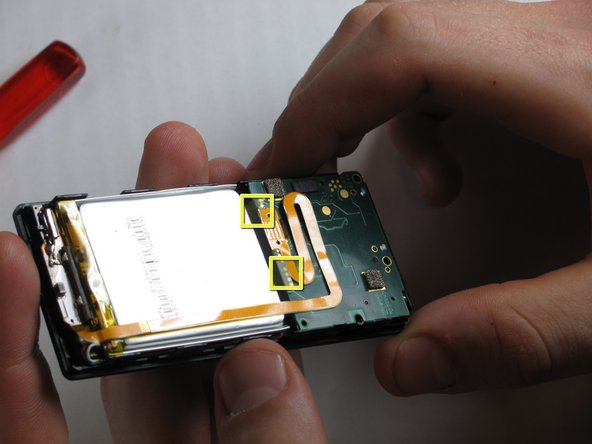 Use your finger or a Zune opening tool to pry back the two clear flaps.