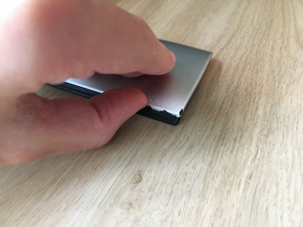 While holding onto the phone with your other hand, insert a clean fingernail into the USB port and pull up on it until the cover pops out of place.