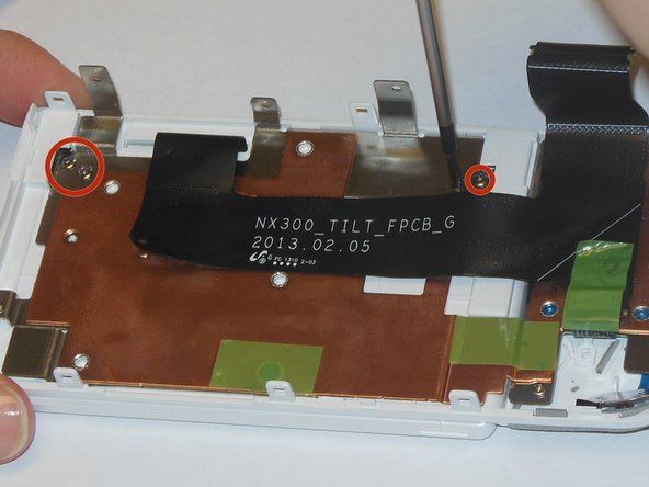 Using a Phillips #00 precision screwdriver, remove the four 1mm screws that are holding the black supports to the panel.
