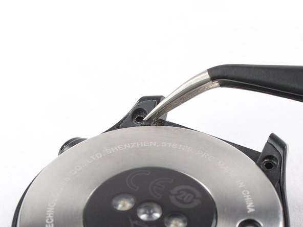 Use a pair of tweezers to remove the four plastic covers sitting next to the watch band holders.