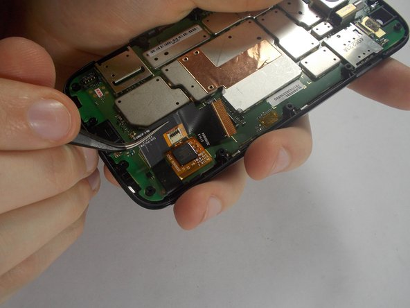Once the ribbon cable is disconnected, use the tweezers to pry it from the mother board.