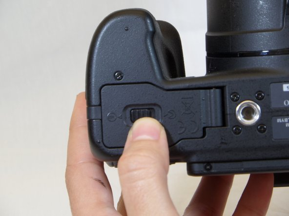 Slide the switch on the battery cover towards the center of the camera.