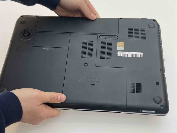 Flip the laptop over onto it's top with the back facing you